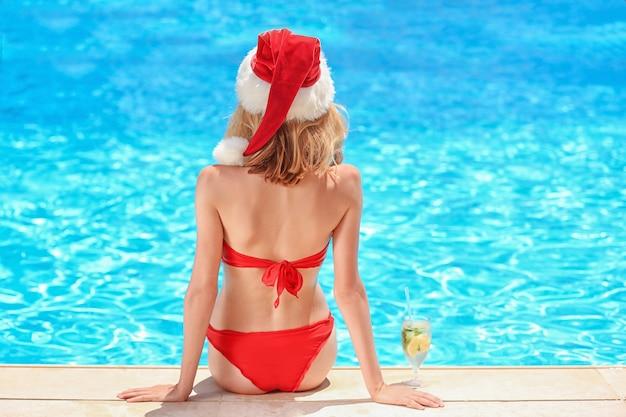 Schöne junge frau mit weihnachtsmütze in der nähe von schwimmbad