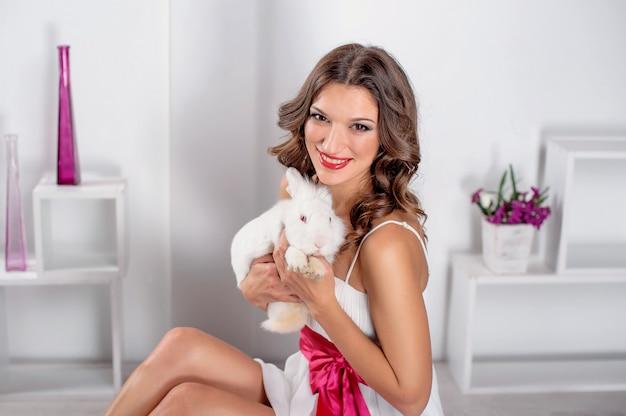 Schöne junge frau mit weißem kaninchen im studio