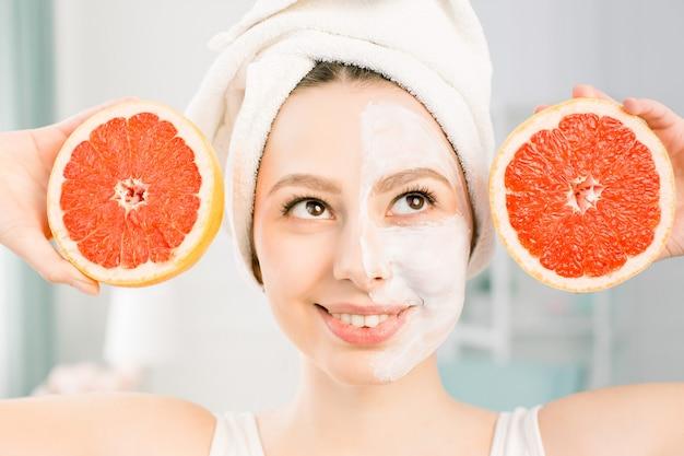 Schöne junge frau mit weißer gesichtsmaske und grapefruithälften auf hellem raum. glückliche frau mit einem weißen handtuch auf ihrem kopf, das eine grapefruit in ihrer hand hält