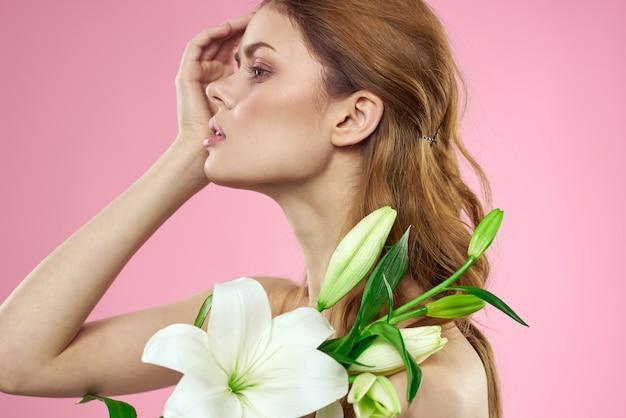 Schöne junge frau mit weißer lilienblume, die im studio auf einem rosa hintergrund, romantisches zartes bild aufwirft