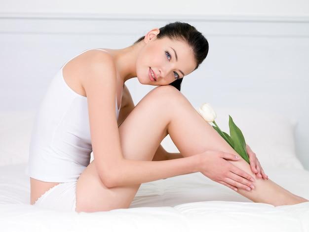 Schöne junge frau mit weißer tulpe auf ihren attraktiven perfekten beinen - drinnen