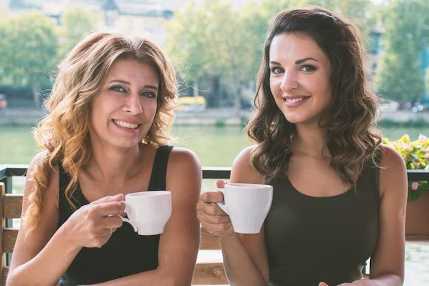 Schöne junge frau mit zwei gerlfriend in einem café mit essen und trinken