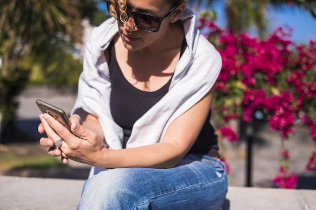 Schöne junge frau mittleren alters schön verwenden sie das telefon, um das internet im freien mit blumen- und naturoberfläche zu überprüfen. lächeln sie an einem perfekten sonnigen sommertag und genießen sie es, verbunden zu sein