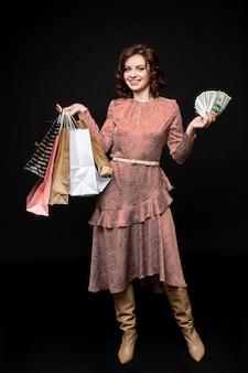 Schöne junge frau nach dem einkaufen steht mit vielen paketen und geld in ihren händen