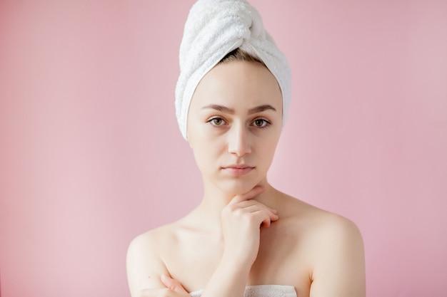 Schöne junge frau nach dusche mit tuch auf rosafarbenem hintergrund