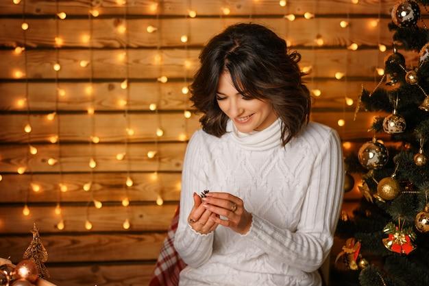Schöne junge frau nahe dem weihnachtsbaum in einer weißen strickjacke