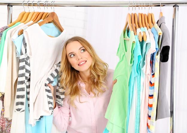 Schöne junge frau nahe gestell mit kleiderbügeln