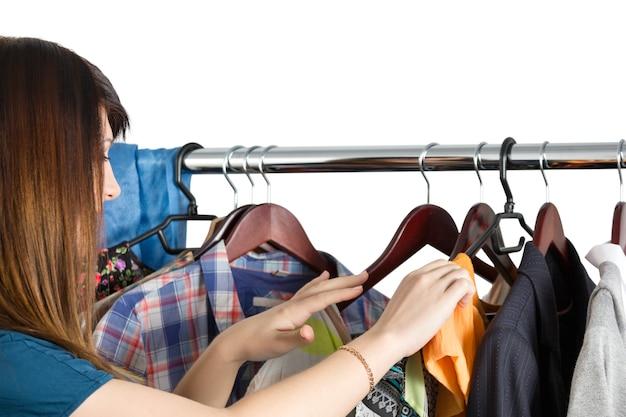 Schöne junge frau nahe gestell mit kleidung, die wählt, was zu nehmen. nichts zu tragen, einkaufs- und verkaufskonzept