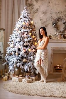 Schöne junge frau nahe weihnachtsbaum, festlicher stimmung, neujahr und weihnachten.