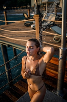Schöne junge frau nimmt an einem sonnigen tag im freien am meer eine entspannende dusche in einem badeanzug. das mädchen im urlaub ruht sich aus. selektiver fokus