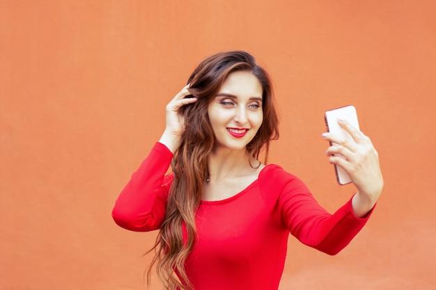 Schöne junge frau nimmt selfie mit smartphone auf orange hintergrund.