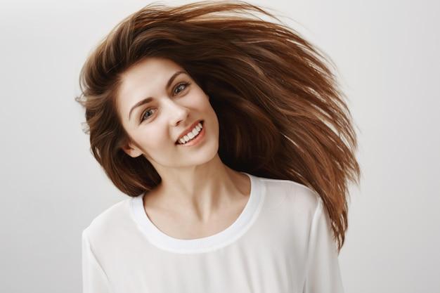 Schöne junge frau peitschen haare und lächeln. haarpflegekonzept