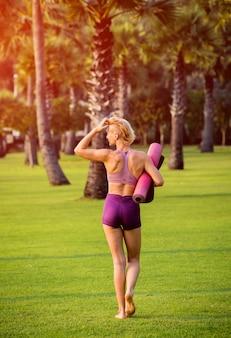 Schöne junge frau praktiziert yoga am strand. übung am frühen morgen