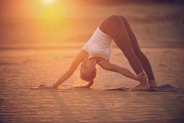 Schöne junge frau praktiziert yoga asana adho mukha svanasana