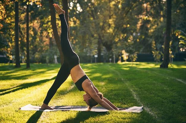 Schöne junge frau praktiziert yoga asana eka pada adho mukha shvanasana - ein bein nach unten hund pose im park