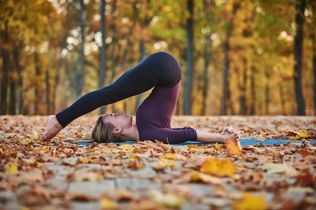 Schöne junge frau praktiziert yoga asana halasana pflug pose auf dem holzdeck im herbst park.