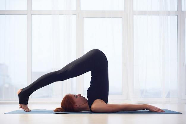 Schöne junge frau praktiziert yoga asana halasana pflug pose im yoga studio.