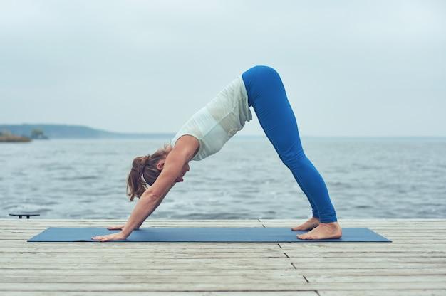 Schöne junge frau praktiziert yoga asana nach unten gerichteten hund auf dem holzdeck nahe dem see