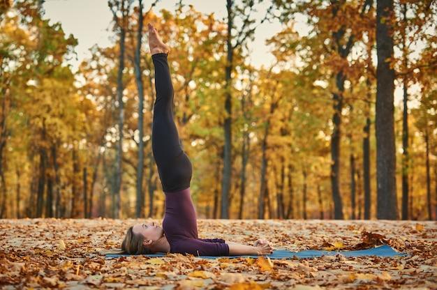 Schöne junge frau praktiziert yoga asana niralamba sarvangasana - nicht unterstützte schulterstandhaltung auf dem holzdeck im herbstpark.