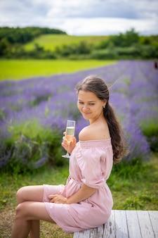 Schöne junge frau ruht auf einem lavendelfeld mit einem glas champagner tschechien