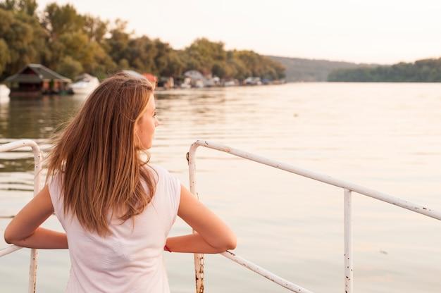 Schöne junge frau schaut auf sonnenuntergang über dem fluss attraktive frau genießt sommer und warmes sonnenlicht. sie bewundern schöne aussicht und genießen sonnenuntergang sonnenlicht. der wind blies ihr haar.