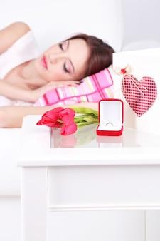 Schöne junge frau schläft auf dem sofa in der nähe des tisches mit geschenken und blumen, nahaufnahme