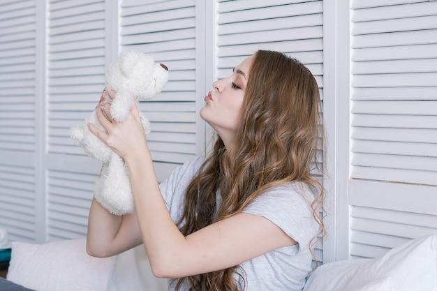 Schöne junge frau sitzt auf dem bett im morgenschlafzimmer