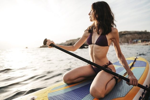 Schöne junge frau sitzt auf einem stand up paddle board im meer bei sonnenuntergang