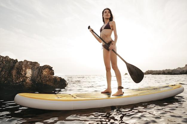 Schöne junge frau sitzt auf einem stand up paddle board im meer
