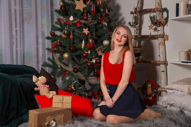 Schöne junge frau sitzt auf einem teppich mit weihnachtsbaum und geschenken