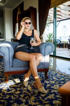 Schöne junge frau sitzt auf einem weichen sessel in der hotellobby mit einem glas champagner im urlaub. sie trägt eine sonnenbrille und ein lächeln im gesicht. urlaubskonzept