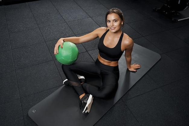 Schöne junge frau sitzt auf matte in schwarzer sportkleidung