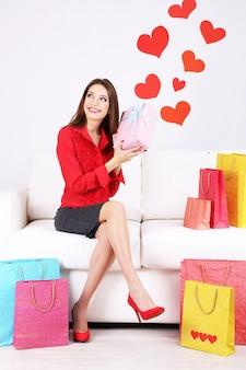 Schöne junge frau sitzt auf sofa mit einkaufstüten und geschenkbox auf grauem hintergrund