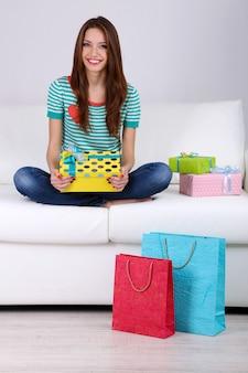 Schöne junge frau sitzt auf sofa mit geschenkbox an grauer wand