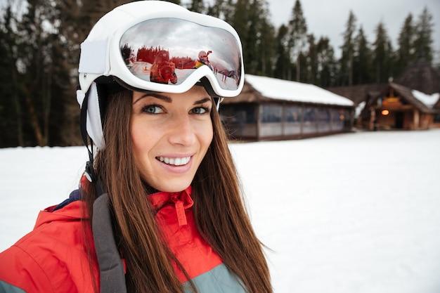 Schöne junge frau snowboarder auf dem frostigen wintertag der pisten
