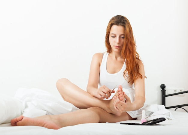 Schöne junge frau sorgt für zehennägel mit nagellack