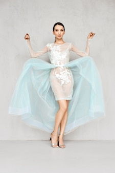 Schöne junge frau spielt mit saum von transparenten tüllkleidern mit spitze