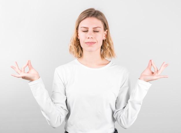 Schöne junge frau steht in meditativer pose, genießt friedliche atmosphäre