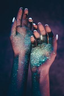 Schöne junge frau tanzt und macht party mit fluoreszierender malerei auf ihrem gesicht. neon-gesichtsporträts