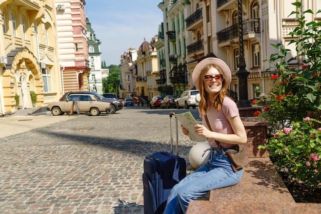 Schöne junge frau tourist angenehm mit stadtplan und koffer im stadtzentrum.