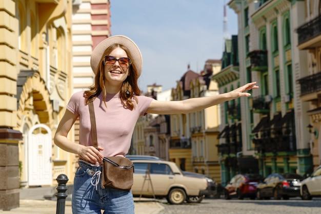Schöne junge frau tourist angenehmer spaziergang in der innenstadt fangen taxi.