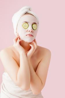 Schöne junge frau trägt eine kosmetische gewebemaske auf ein gesicht mit gurke auf einem rosa auf.