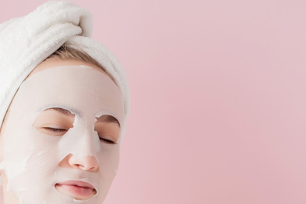 Schöne junge frau trägt eine kosmetische gewebemaske auf einem gesicht auf einem rosa auf. gesundheits- und schönheitsbehandlung sowie technologiekonzept