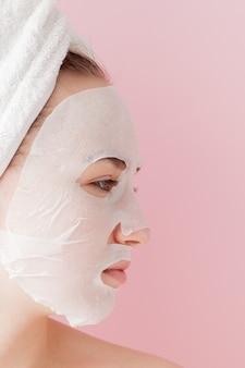 Schöne junge frau trägt eine kosmetische gewebemaske auf einem gesicht auf einem rosa auf.