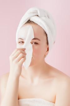 Schöne junge frau trägt eine kosmetische gewebemaske auf einem gesicht auf rosa auf
