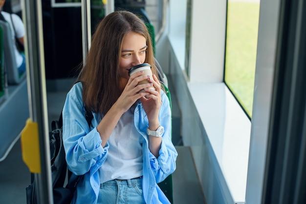 Schöne junge frau trinkt köstlichen kaffee im stadtbus oder in der straßenbahn. konzept des öffentlichen verkehrs.