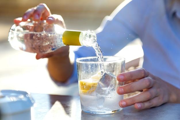Schöne junge frau trinkt soda in einem restaurant terrasse.