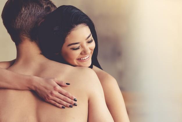 Schöne junge frau umarmt ihren mann und lächelt