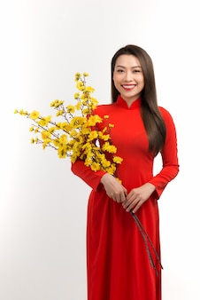 Schöne junge frau und aprikosenblüte, vietnamesische tet-urlaubsbeschaffung
