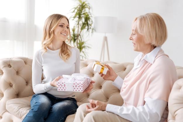 Schöne junge frau und ihre ältere mutter sitzen auf dem sofa und halten kisten mit geschenken, während die tochter ihre mutter anlächelt
